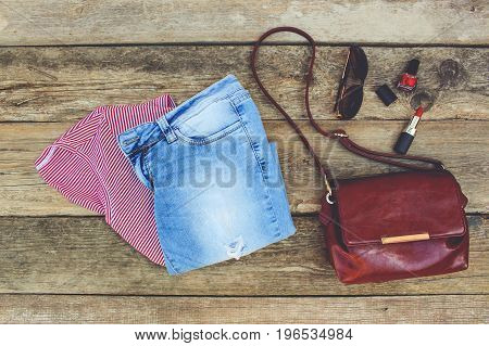 Women's summer clothing and cosmetics on old wooden background. Toned image. Top view.
