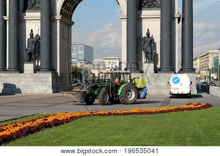 Moscow Russia - July 21 2017: Tractor near Triumphal Arch of Moscow during flower planting work in a city.