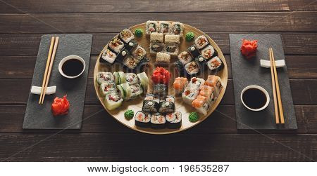Japanese restaurant, sushi roll platter on rustic wood background and black slate plates. Set for two with chopsticks, ginger, soy, wasabi.