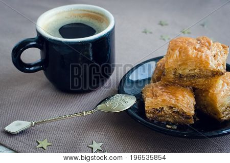 Turkish national delight baklava with pistachios walnuts and honey and cup of coffee on a white wooden background. Traditional eastern dessert.