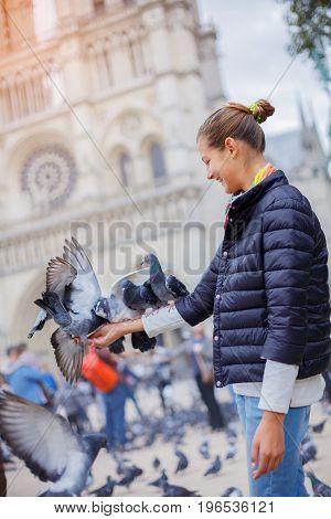 Girl with pigeon birds near Notre Dame de Paris cathedral in Paris, France