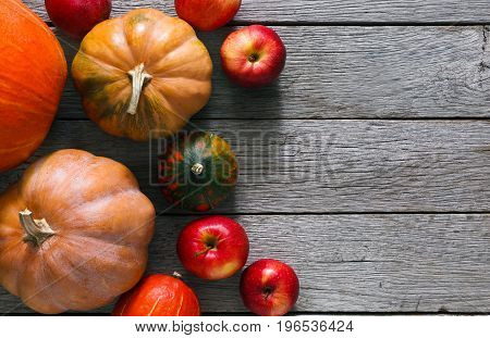 Autumn harvest background. Top vivew, pumpkins and red apples on weathered rustic gray wood with copy space.