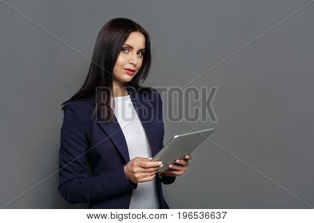 Concentrated woman using digital tablet on gray background. Communication concept