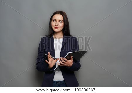 Confident elegant business woman in formal suit standing with notepad on gray studio backgroundand dreaming, looking away, copy space