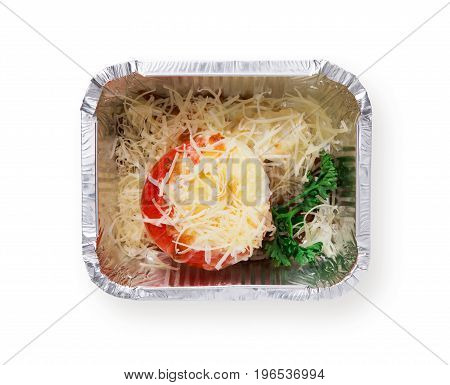 Healthy food isolated at white background. Daily slimming menu. Organic restaurant food take away and delivery. Baked tomatoe with low fat cheese and greens in foil box, top view