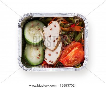 Healthy food in take away box isolated at white background. Dietary restaurant food delivery. Steamed chicken with backed vegetable salad of asparagus, tomatoe and flax seeds, top view