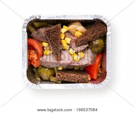 Healthy food in foil box isolated at white background. Daily slimming menu. Organic restaurant food take away and delivery. Steamed meat with vegetable salad, rye bread and corn, top view