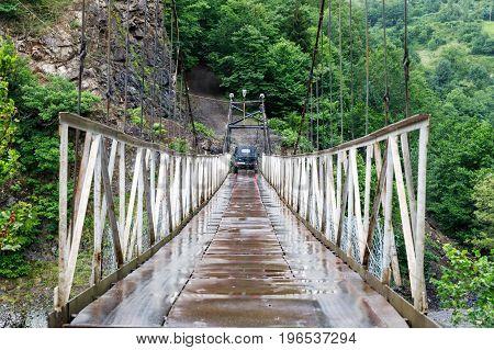 Suspension bridge. Old car on the car bridge across a mountain river during a rain in Georgia