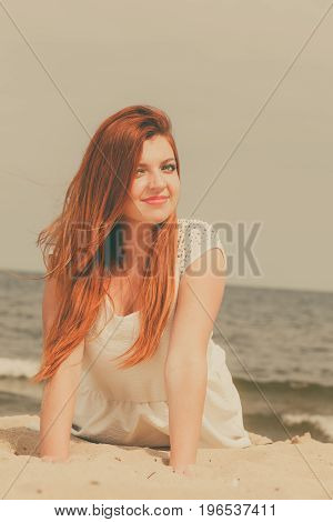 Summer relaxation and recreation concept. Happy redhead adult woman lying on beach during summertime.