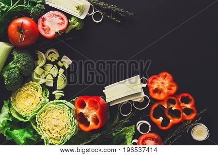 Cooking healthy vegetables background. Fresh organic food, peppers, leek and greens on black. Natural food with copy space.