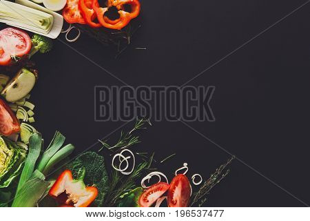 Vegetables border background. Fresh organic food, peppers, leek and greens on black. Natural food with copy space.
