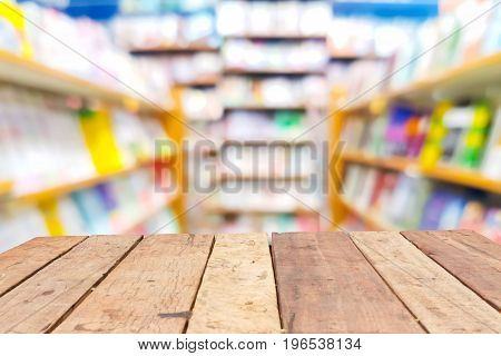 perspective wooden board empty table in front of blurred background of shelves in bookstore or library. can be used for display or montage your products. Mock up for displaying product.