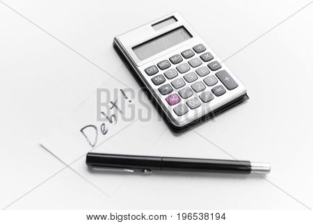 calculator with a pen and paper note with word debt isolated on white background