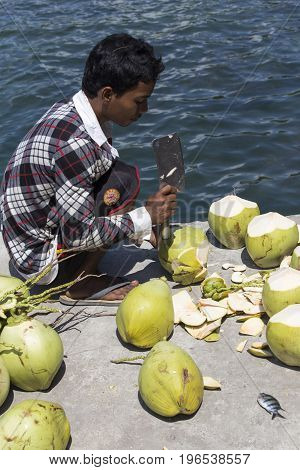 An Unidentified Man Cutting Coconuts