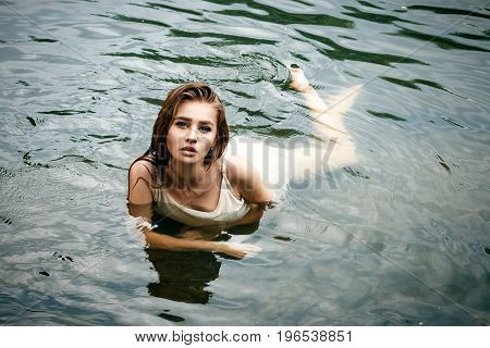 Passionate sexy female girl dressed in a light negligee bathes lies in the river wet and very beautiful