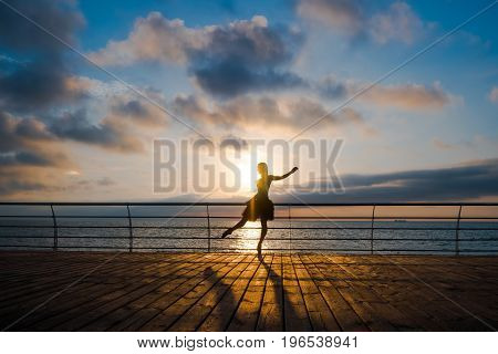 Silhouette of dancing ballerina in black ballet tutu and pointe on embankment above ocean or sea at sunrise or sunset. Young attractive blonde woman with long hair practicing stretching and exercises.