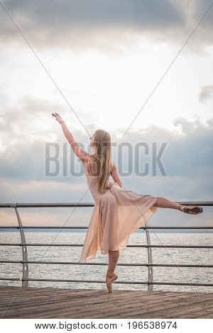 Dancing ballerina in beige silk dress and pointe on embankment above ocean or sea beach at sunrise. Young beautiful blonde woman with long hair practicing classic exercises with emotions.