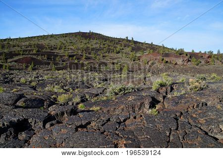 Three types of black volcanic basalt rock: cinder cone, formed by small porous pebbles, relatively smooth pahoehoe lava, aa lava chunks of relatively angular pieces of lava. Craters of the Moon.