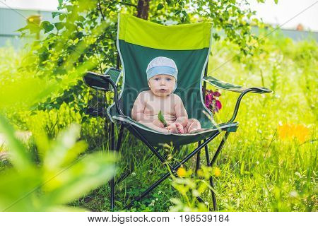 Cute Blond Baby Boy Enjoying The Sun Sitting On Chair In A Garden