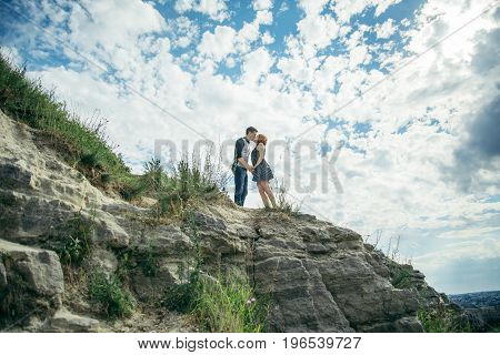 young man and woman kissing on the peak of the hill
