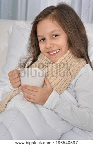 cute little girl lying in bed with white cup of tea