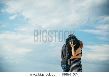 woman kiss boyfriend while hiding behind the hat , clouds on background
