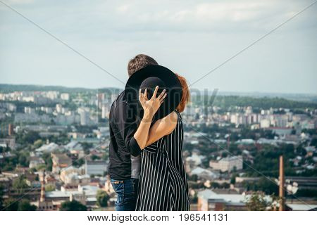 woman kiss boyfriend while hiding behind the hat , clouds with city on background