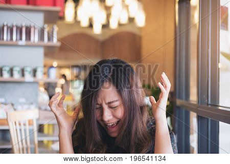Close up image of an Asian woman close her eyes and scream with feeling angry in restaurant
