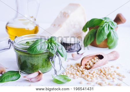Pesto genovese - traditional Italian green basil sauce with raw ingredients on white wooden background. Basil leaves in mortar Parmesan cheese pine nuts olive oil garlic and salt.