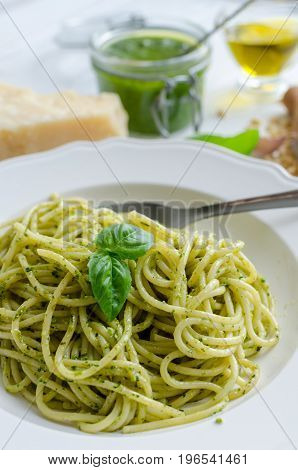 Spaghetti with homemade pesto sauce on white wooden table. Pasta with pesto alla genovese. Italian cuisine concept.