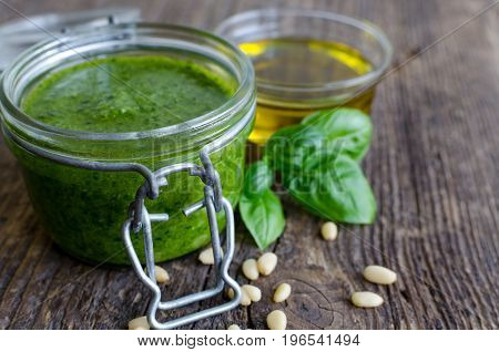 Pesto genovese - traditional Italian green basil sauce with olive oil basil leaves and pine nuts on old wooden background.
