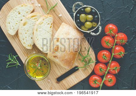 Sliced freshly baked ciabatta bread on wooden cutting board with rosemary olive oil tomatoes olives and salt on dark stone black concrete table. Italian food concept. Top view.