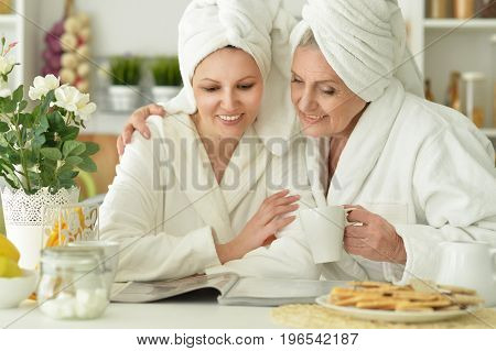 Senior woman and  daughter  in a bathrobe with magazine and tea