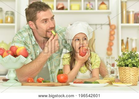 family together on the kitchen, man and girl eating