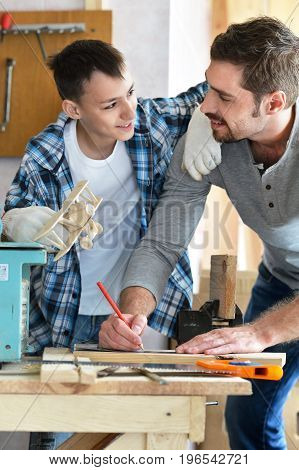 happy father and son processing wood in carpentry workshop
