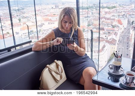 Young blond woman in casual stlye dress using tablet while sitting in a rooftop cafe with amazing view over big city