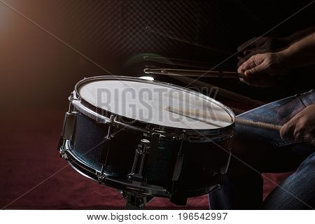The Man Is Playing Drum Set In Low Light Background.