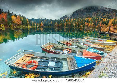 Fantastic colorful boats on the alpine lake near Slovenian-Italy border Lake Fusine Italy Europe