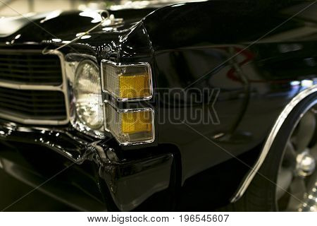 Headlight of a black classic retro american car.The front lights of the car and alloy wheel. Classic Retro Car exterior details.