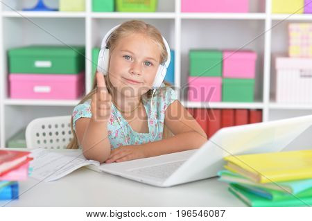 Cute girl in headphones sitting at table with laptop