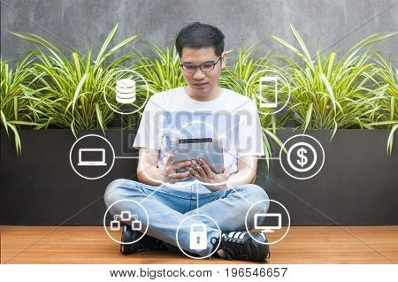 Asian Young Man In Casual Dress Wear Glasses Connected Cloud Technology In Digital Tablet At Coffee