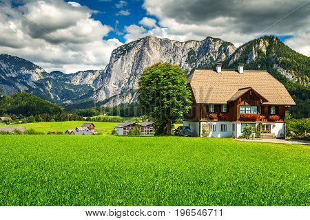 Amazing summer landscape with green fields alpine farmland pasture and high rocky mountains in background Altaussee Salzkammergut Austria Europe