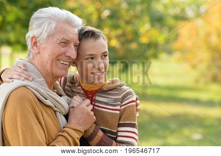 Outdoor portrait of grandfather and grandson in autumnal park