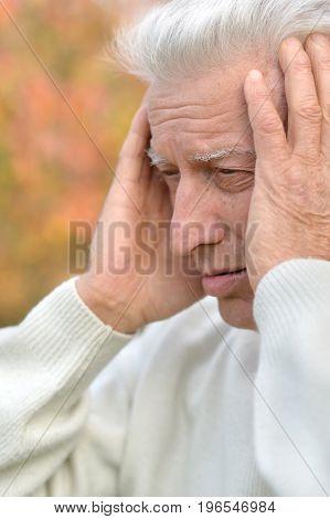 Sad  elderly man posing  in autumn park