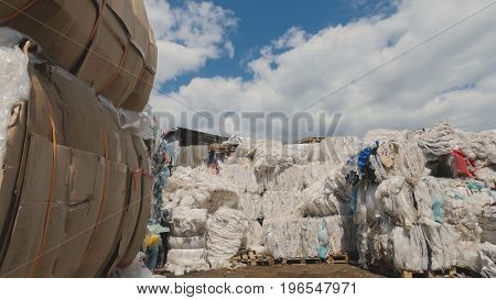 On the territory of the recycling plant. Against the blue sky, heaps of plastic debris lie