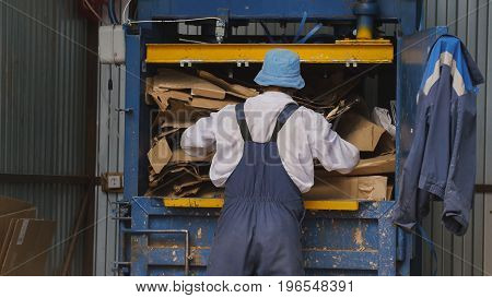 Worker on recycling of cardboard at industrial landfill, ecology concept, telephoto