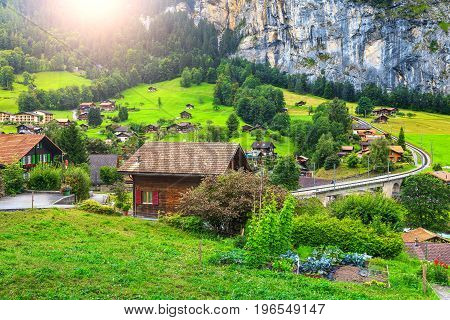 Amazing green fields and famous stunning touristic town with high cliffs in background Lauterbrunnen Bernese Oberland Switzerland Europe