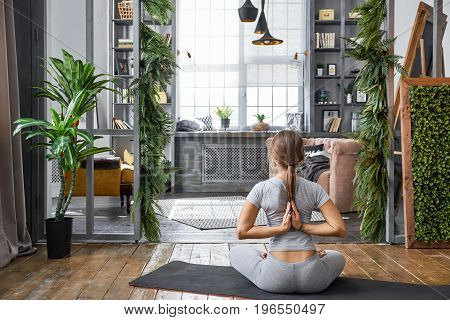 Woman practicing advanced yoga in the living room at home. A series of yoga poses.