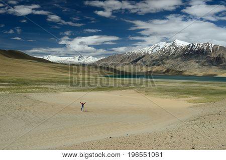 Tourist traversing the desert in the vicinity Tso Startsupuk Lake in the Karakorum Mountains near Leh India.