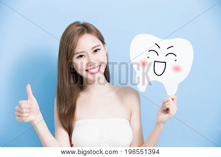 woman take cute tooth and thumb up on blue background